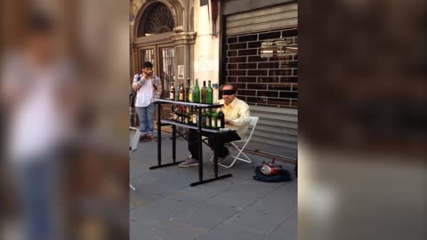 Blindfolded street performer plays music on bottles
