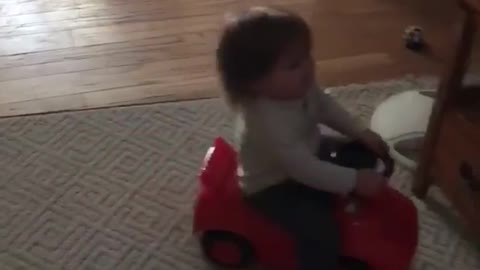 Small kid on red toy motorcycle falls back