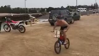 Guy rides his bike off a ramp into a lake