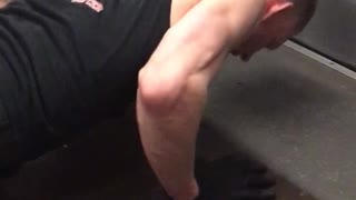 Tank top guy does pushups on the floor of subway