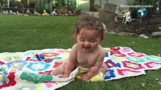Blue ball thrown at baby sitting on grass