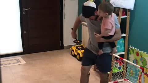 Dad performs golf trick shot challenge while holding his son