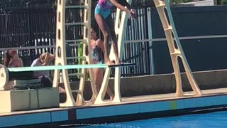 Girl in pink jumping into pool belly flops