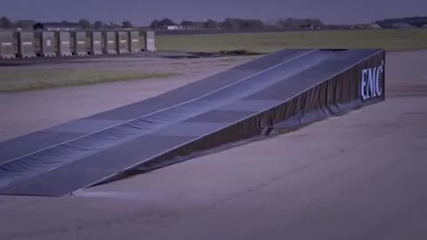 Truck jumps over moving F1 car!