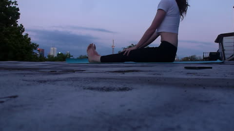 Girl does yoga on the roof