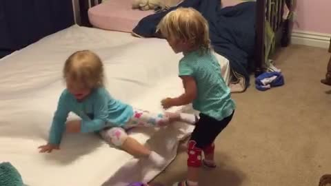 Identical twin toddlers tickle each other