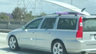 Grey silver car carrying white surf board