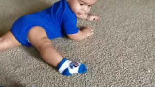 Baby Boy Spins Around Floor Chasing His Foot - Video