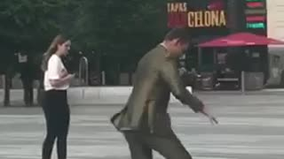 Guy in suit tries to ride skateboard and falls onto pavement  - Video