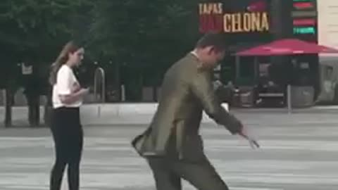 Guy in suit tries to ride skateboard and falls onto pavement