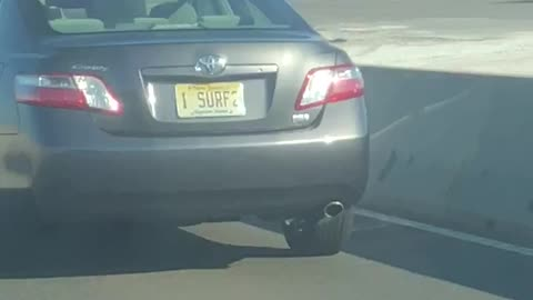 Guy screaming driving by car with i surf 2 license plate