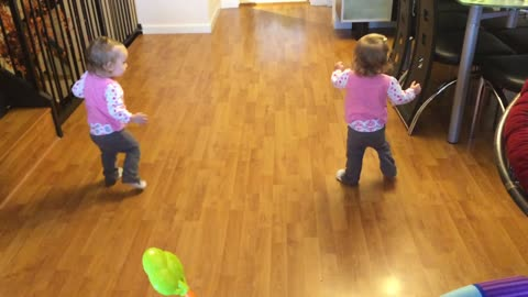 Identical twin babies walk simultaneously together