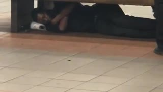 Guy in all black sleeping under bench subway underground  - Video