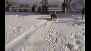 Two Girls On Sled Crash Into The Side Of A House - Video