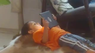 Little boy plays with tablet while lying on top of Golden Retriever