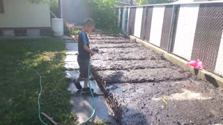 dad teaches son how to water the garden. - Video