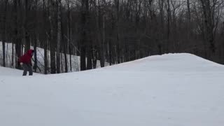 Skier skis off ramp and lands on back and butt, skis fly off feet