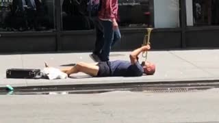 Man plays trumpet on floor of street - Video