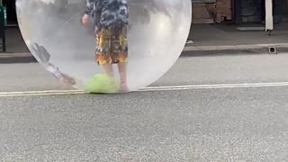 Performer Sings in Bubble While Rolling Down the Road