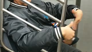 Man waves air into his face with his hands on subway train