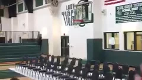 Kid holds onto basketball net lands on back