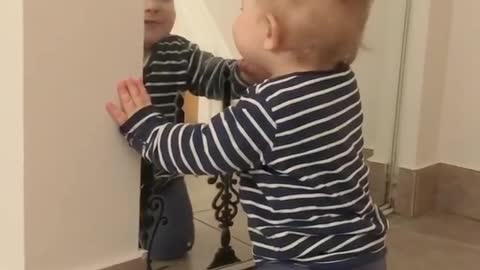 Sweet baby talks to his reflection in the mirror