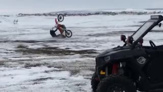 Guy red motorcycle wheelie snow fall