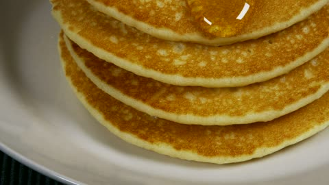 Honey pouring over pancakes