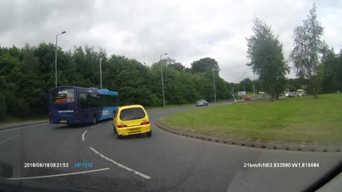 Reckless driver barely passes bus on roundabout