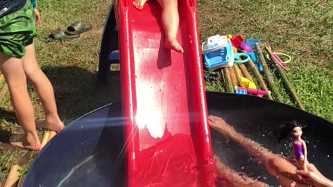 Brother unexpectedly pushes little sister down water slide