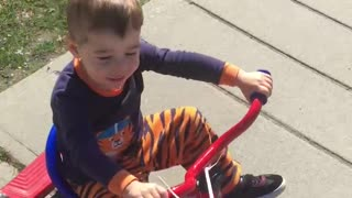My grand son riding tricycle around my neighbourhood