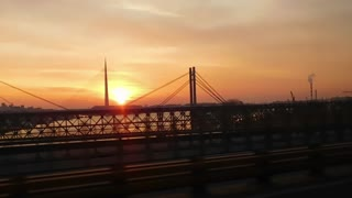 Driving Vehicle Over a Bridge During Amazing Sunset