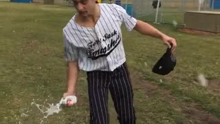 Guy in baseball uniform cracks beer over head  - Video