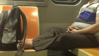Man sits with no shoes on on subway