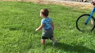 Big brother knocks over toddler while riding his bike