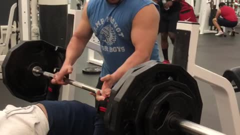 Guy very heavy bench press, bar falls off rack and almost crushes him