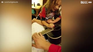 Tender moment when a father and his daughter share a guitar - Video