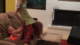Little boy orange shirt launches little girl green shirt with legs - Video