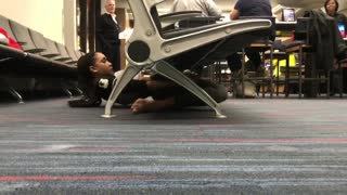 Young Woman At An Airport Limbos Under A Chair - Video