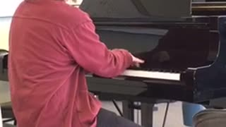 Glasses red shirt plays microsoft theme on the piano - Video