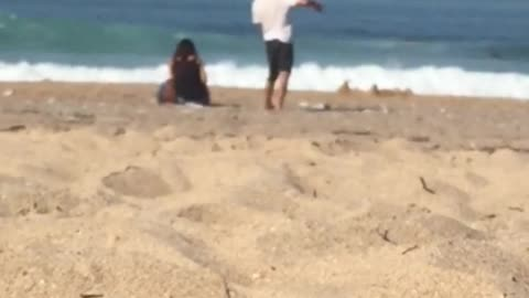 Guy gently dances by himself at the beach