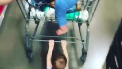 Kid holding onto shopping cart dragged across floor