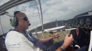 Skilled pilot touches ground with stunt plane wing - Video