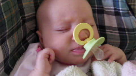 Adorable baby gets pacifier stuck on nose