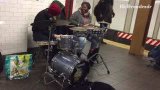 Man and woman play drums on subway platform