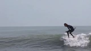 White board black suit surfer falls off - Video