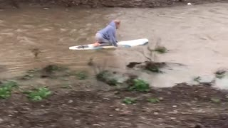 Girl rides surfboard down rain filled drainage ditch - Video