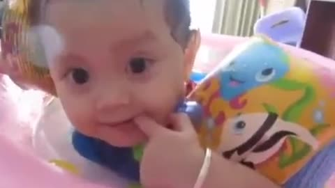 Cute baby playing in the indoor pool