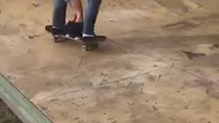 Guy skateboards with toddler holding unto him  - Video
