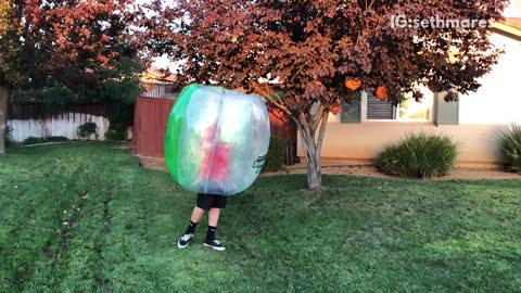 Teen kicks guy in bubble suit on grass